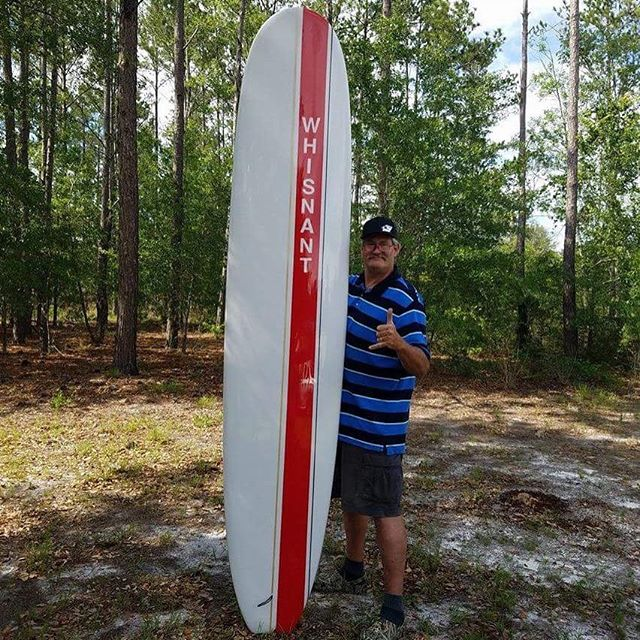 """My buddy Neal with his new custom board. The board is 10' and Neal is 6'9""""."""